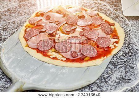 Uncooked salami pizza on pizza peel. Pizza peel taking uncooked pizza from table.