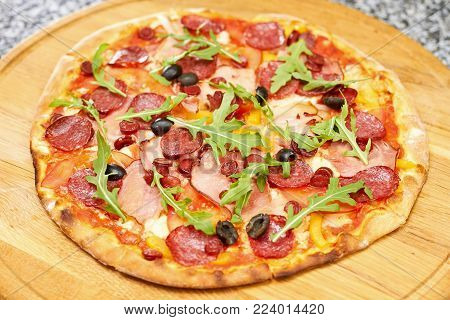 Pepperoni pizza with fresh ingredients, top view. Pepperoni pizza on wooden plate.