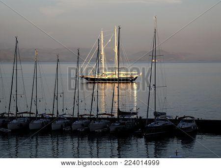 Golden schooner in the rays of the setting su
