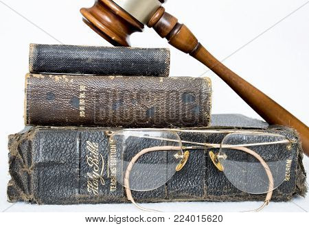 Close Up Three Antique Bibles with Antique Rimless Glasses and Gavel on White Background