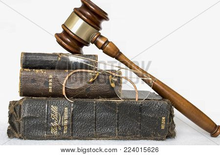 Three Worn Antique Leather Bibles Stacked with Rimless Glasses and Wooden Gavel on White Background