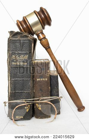 Three Antique Leather Bibles with Rimless Antique Glasses and Wooden Gavel on White Background