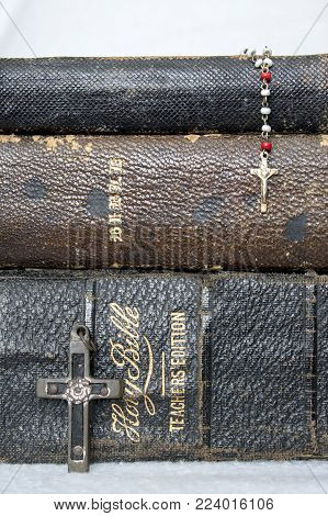 Stack of Worn Leather Bibles with Antique Cross and Antique Rosary