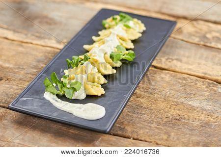 Row of ravioli on black rectangle plate. Decorated ravioli dish.