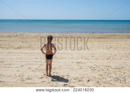 Six-year-old boy in swimming trunks stands on the beach and gazes out to sea. Hands on his belt.
