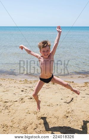 Six-year-old boy in black speedo jumping into the sea and laughs. Jump high off the ground.