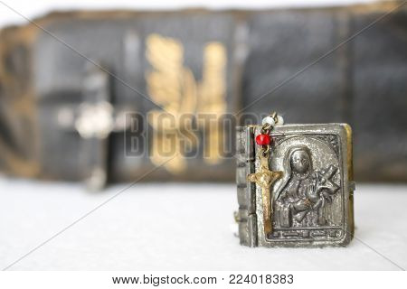 Small Antique Rosary with Case in Foreground and Leather Antique Bible in Background