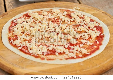 Closeup smeared ketchup with shredded cheese on pizza crust. Sprinkled shredded cheese on pizza dough.