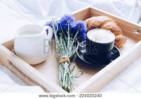 Romantic summer breakfast in bed, tray with fresh croissant, cup of coffee espresso with milk and bouquet of blue cornflowers. Good morning concept. Enjoy slow life. Traditional continental breakfast.
