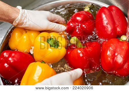 Hands in gloves washing peppers into bowl, close up. Rinsing vegetables into metal bowl.