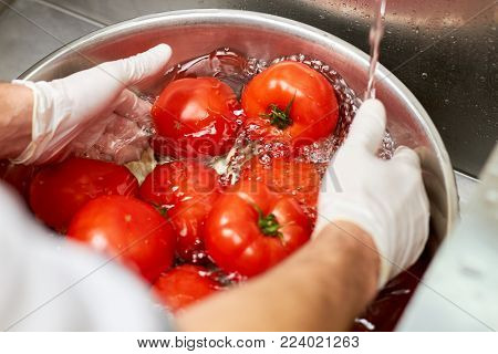 Washing big red tomatoes in bowl. Hands rinsing tomatoes in metal basin.