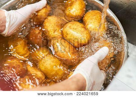 Washing potatoes piles under running water. Close up chef hands washing heap of potatoes in metal basin.