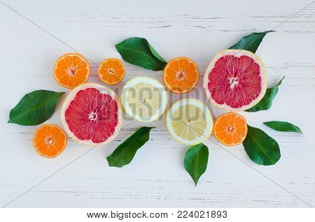 Mixed citrus background. Assorted fresh citrus fruits with leaves on white wooden table. Lemon, grapefruit, mandarin. Harvest concept. Healthy eating, dieting. Top view.