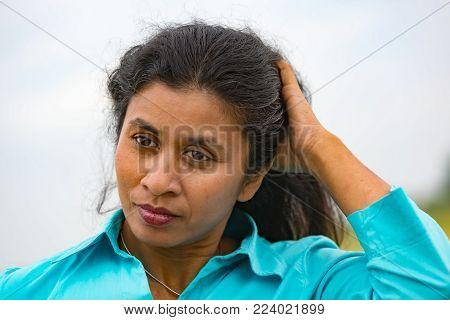 Asian woman put her Hand through her hair - outdoor shot