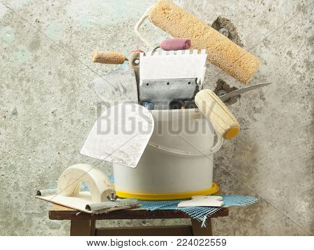 Plastic bucket and set of plaster trowel tools and spatula on background old wall. Renovation concept.