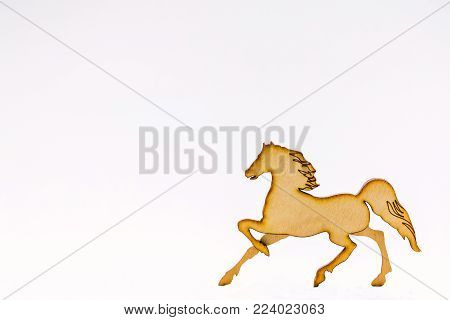 Horse, carved from wood, with developed mane and tail, on white background, Wooden horse decor, cooked from solid wood. Winter, Christmas, New Year, events, wooden pine finish. Isolated on white background. Side view