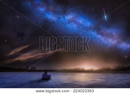 Night astrophotography landscape with man sitting on snow and watching stars.