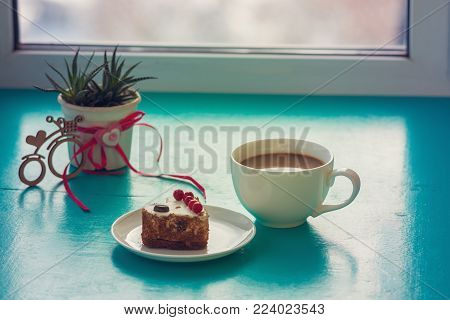 Valentine's Day, breakfast for your favorite - cup of coffee, with a heart shaped cake, stands on a green surface, next to a cactus and a bicycle symbol with a heart on window blurred background.