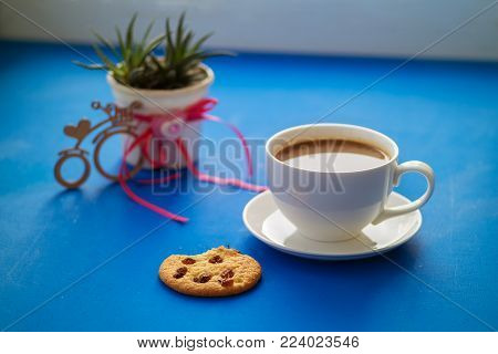 Valentine's Day, breakfast for your favorite - steaming cup of coffee with a cookies stands on a blue surface, next to a cactus and a bicycle symbol with a heart. Top view.