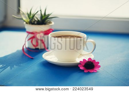 Valentine's Day, breakfast for your favorite - steaming cup of coffee stands on a blue surface, next to a cactus with a heart symbol and a red flower on the window blurred background.