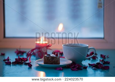 Valentine's Day, romantic dinner - big cup of coffee and cake are standing on a green surface with pink rose petals next to  burning candle with a heart symbol on window blurred background.