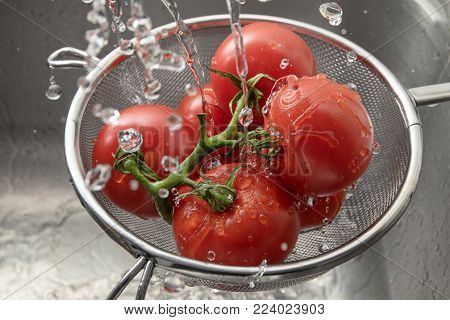 fresh tomatoes in a metal cullender among many drops of water, washing and preparing healthy food