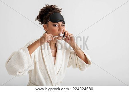 Playful quiet lady in bathrobe taking care of her oral cavity and using cellphone. She is winking at camera. Isolated on background