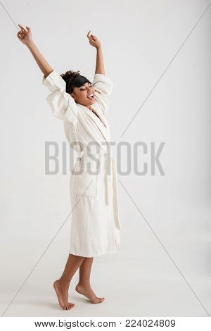 Pleased girl with slim body standing in bathrobe. She is holding her hands up and gaping poster