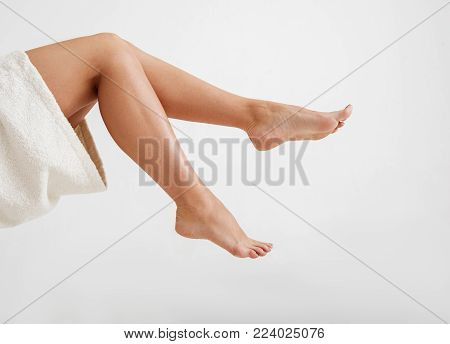Care concept. Close up of female hairless soft feet. Isolated on background
