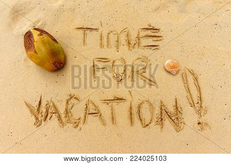 time for vacation written on the sand with coconut and seashell. Creative travel concept