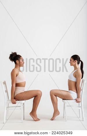 Side view profile of glad girls with graceful bodies in lingerie. They are sitting on chairs opposite each other and smiling. Isolated on background