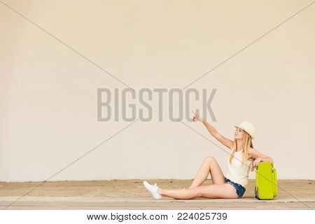 Travel, adventure, teenage journey concept. Woman wearing denim shorts, white top and sun hat suitcase holding suitcase on wheels sitting and pointing at something