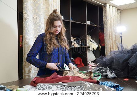 The girl is a seamstress working in a sewing workshop.