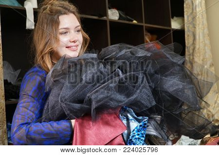 Seamstress, costumier or seller holding a bunch of dresses. Portrait of woman in Studio.