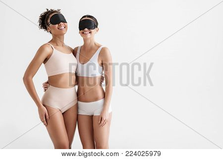 Portrait of slim women wearing tight underwear and black sleep masks. They are hugging and smiling. Copy space in right side. Isolated on background