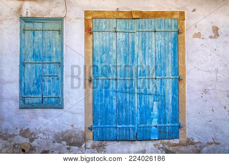 Old greek house with old blue door and window. Old blue weathered door and window in Cyprus.