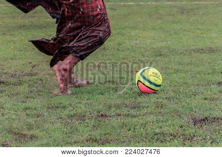Labuan,Malaysia-Jan 18,2018:Group of man in traditional costume called sarongs playing traditional games village football in Labuan,Malaysia.A sarong or sarung is a large tube or length of fabric worn in Southeast Asia.