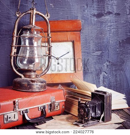 vintage travel still life with kerosene lamp, book, old camera and suitcase
