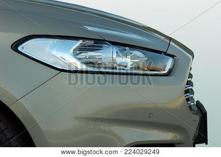 Headlight of modern prestigious car closeup, side view