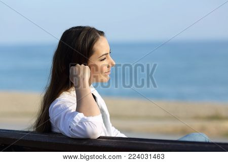 Portrait of a pensive woman looking away sitting on a bench on the beach