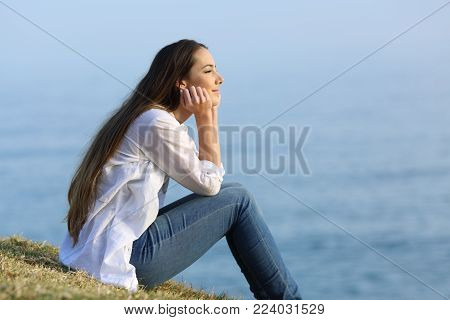 Side view portrait of a happy woman relaxing sitting on the grass watching the sea in the background