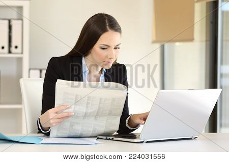 Concentrated businesswoman working comparing a newspaper with online content in a laptop on a desktop at office