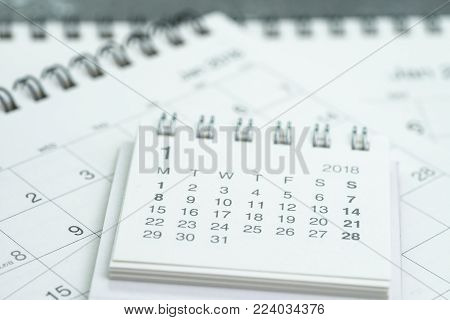 Clean white calendar business deadline, time passing, year planning or appointment reminder concept by pile of white and clean paper calendars on office table.