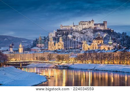 Beautiful view of the historic city of Salzburg with Salzach river in winter during blue hour, Salzburger Land, Austria