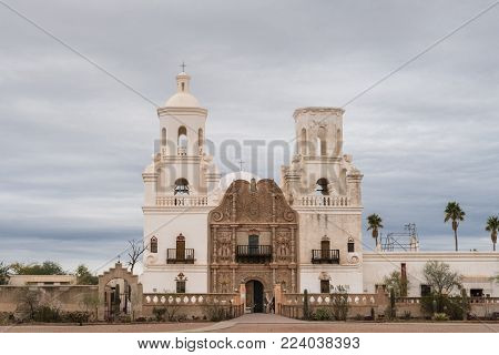 Tucson, Arizona, USA - January 9, 2018: White and brown front facade of Historic San Xavier Del Bac Mission under heavy gray, white cloud deck. Some greenish desert plants in front.