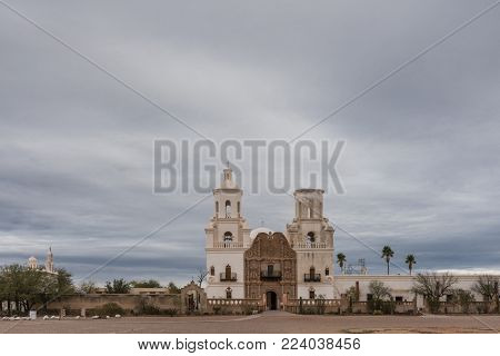 Tucson, Arizona, USA - January 9, 2018: Wide view on White and brown front facade of Historic San Xavier Del Bac Mission under heavy gray, white cloud deck. Some greenish desert plants in front.