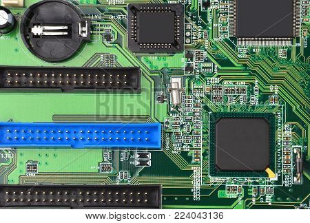 Green printed computer motherboard with microcircuit, close-up