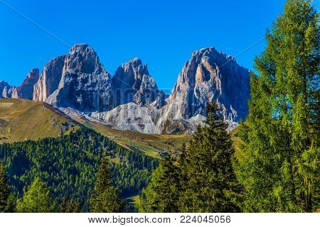 The most picturesque route in the Italian Dolomites, the Southern Limestone Alps. The coniferous forests at the foot of limestone and dolomite rocks. The concept of active and car tourism