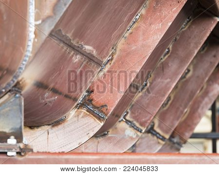 Large steel tank with welded on reinforcement beams under construction. Shallow depth of field with the nearest reinforcement beam in focus.