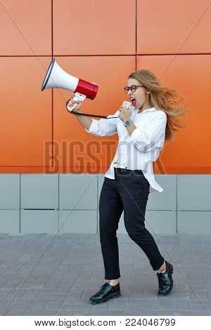 A young attractive girl in a white shirt and glasses is holding a loudspeaker in her hands. She's screaming. Promotional action on the street